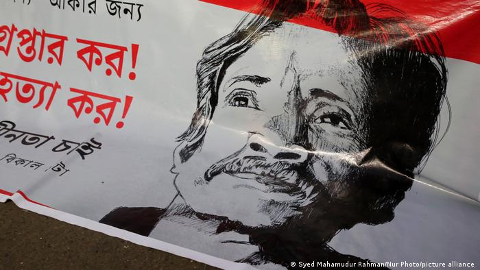 A protest placard with Mushtaq Ahmed's portrait on it