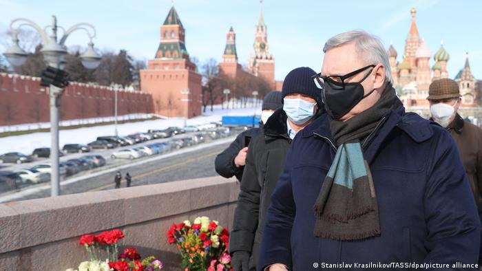 Parnas Party leader Mikhail Kasyanov (front) lays flowers at the site of Boris Nemtsov's assassination.