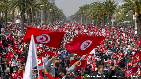 Protesters gather in the Tunisian capital Tunis waving national flags