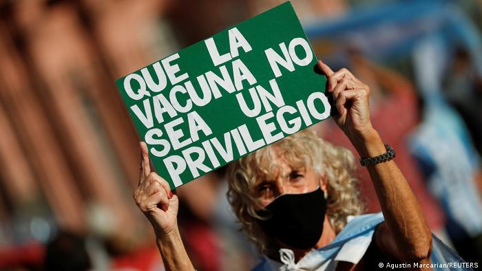 Foto de manifestante con un rótulo que dice que la vacuna no sea un privilegio en Argentina