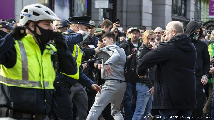 Eine aufgebrachte Menge gerät bei Protesten in Dublin gegen die Corona-Maßnahmen | mit Polizeikräften zusammen