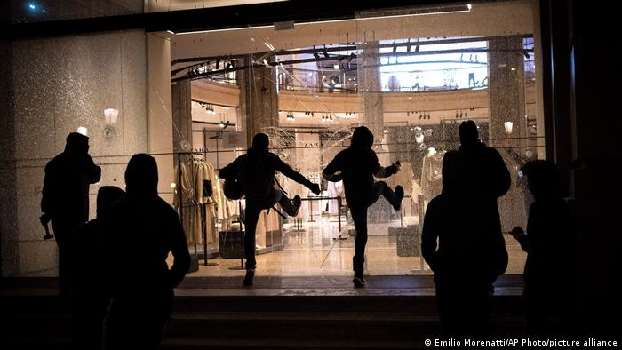 Protesters break the windows of a shop during clashes following a protest condemning the arrest of rap singer Pablo Hasél in Barcelona, Spain
