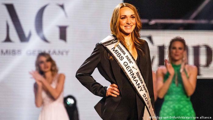 Anja Kallenbach mit der Miss Miss Germany 2021 Schärpe, im Hintergrund zwei klatschende weitere Kandidatinnen