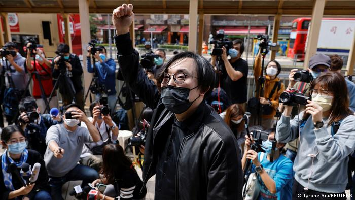 Pro-democracy activist Mike Lam King-nam raises his fist on arrival at the police station. He is surrounded by press. He is wearing a black jacket and black medical face mask
