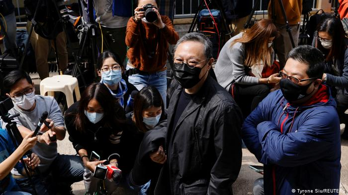 Benny Tai arrives at a police station in Hong Kong. He is surrounded by press. He is wearing a black, formal jacket