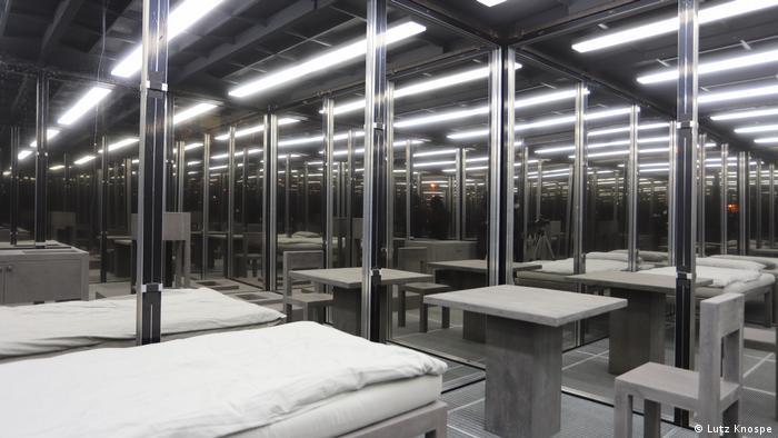 Ein riesiger Raum voll mit leeren Tischen und leeren Notbetten, darüber Neonlicht-Röhren an der Decke.
