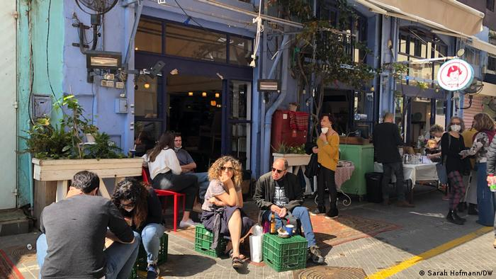 People sit outside a cafe in the sun on beer crates