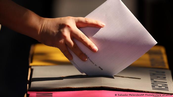 Foto simbólica de una mano con una papeleta de votación en El Salvador
