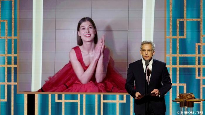 Rosamund Pike lächelt in einem roten Kleid, als sie mit einem Golden Globe ausgezeichnet wird.