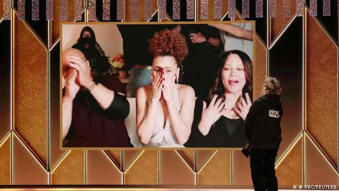 Andra Day erhält den Golden Globe und schlägt die Hände vor dem Gesicht zusammen.