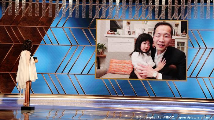 Director Lee Isaac Chung picured on-screen with his daughter sitting in his lap during the awards ceremony.