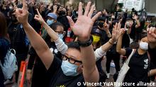 Supporters gesture with five fingers, signifying the Five demands - not one less outside a court in Hong Kong Monday, March 1, 2021