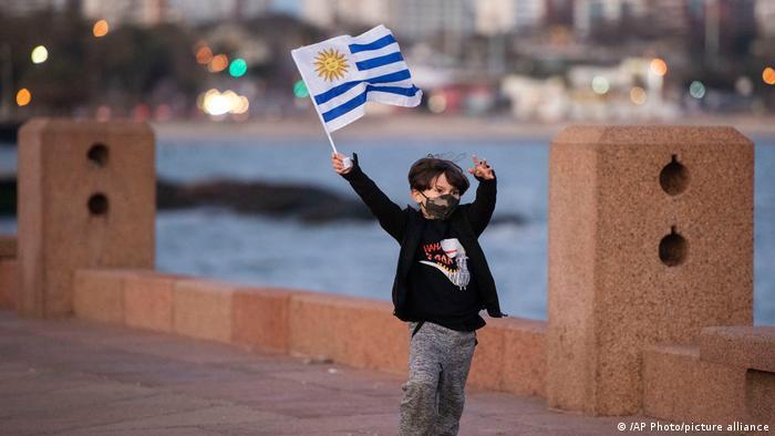 Foto de un niño con mascarilla que juega con una bandera de Uruguay