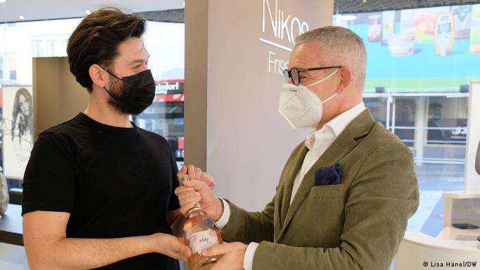 Hairdresser Nikos Kasapidis (l) welcomes regular customer Stefan Sorce