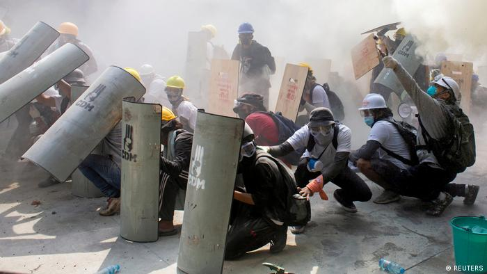 Myanmar anti-coup protesters in a cloud of tear gas