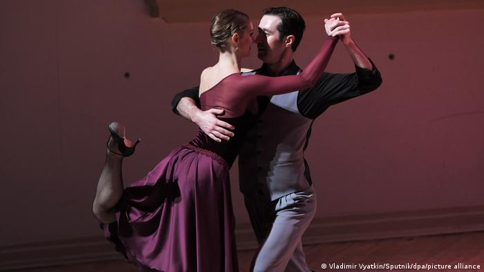 Couple dancing the tango, with woman's leg kicked up behind her.
