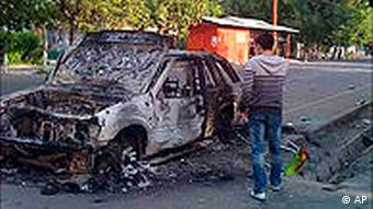 A man examines a burnt car in Osh