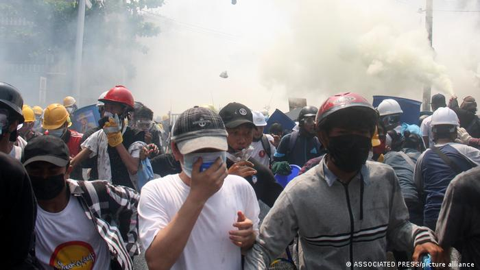 Protesters run away from tear gas launched by security forces during an anti-coup protest in Mandalay on Tuesday, March 2. Protesters across the country wore hard hats and makeshift shields, and gathered behind barricades while chanting and sporting the three-finger salute.