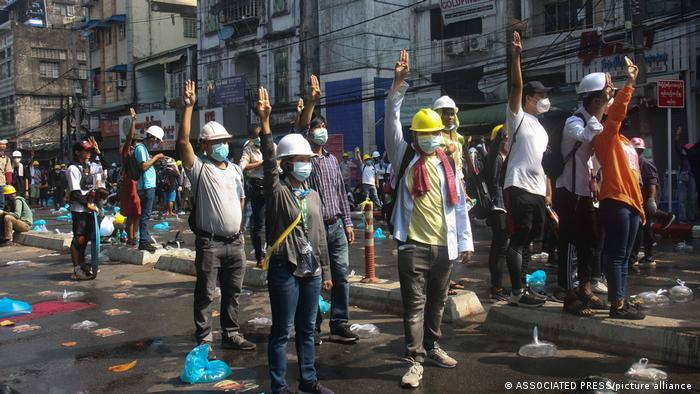 Protesters wearing safety helmets shout slogans and flash three-finger salutes during a protest on a blocked road in Yangon on Tuesday, March 2. There were no reports of any injuries in Yangon on Tuesday, but, according to witness reports, several people were injured in the northwestern town of Kale when police fired live ammunition to disperse a crowd.