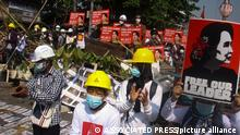 Protesters wearing safety helmets shout slogans and display images of deposed Myanmar leader Aung San Suu Kyi during an anti-coup protest behind a barrier on a blocked road in Yangon, Myanmar, Tuesday, March 2, 2021. Demonstrators in Myanmar took to the streets again on Tuesday to protest last month's seizure of power by the military, as foreign ministers from Southeast Asian countries prepared to meet to discuss the political crisis. Police in Yangon, Myanmar's biggest city, used tear gas against the protesters. (AP Photo)