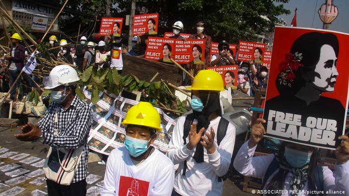 Protesters wearing safety helmets shout slogans and display images of deposed Myanmar leader Aung San Suu Kyi during an anti-coup protest behind a barrier on a blocked road in Yangon, on Tuesday, March 2. Demonstrators took to the streets as Southeast Asian foreign ministers prepared to meet to discuss the crisis.