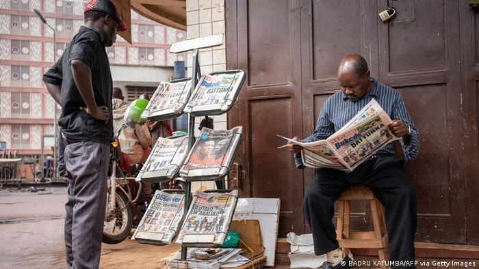 Ein Mann liest eine Zeitung neben einem Zeitungsstand