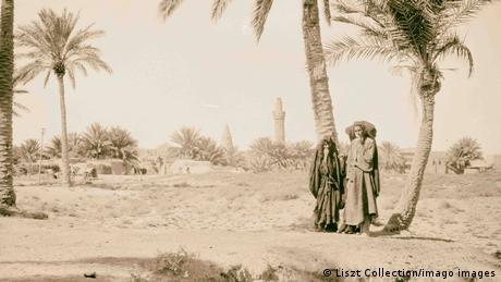Ein Schwarz-Weiß-Foto von 1932, Ein Paar steht vor Palmen, im Hintergrund ein Minarett