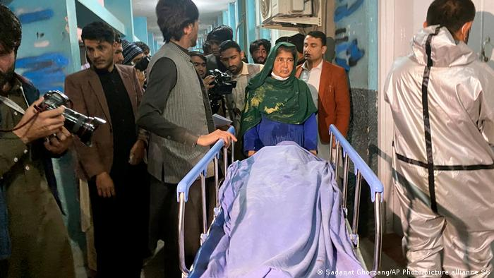 Afghans carry the body of a woman who was killed by gunmen in the city of Jalalabad east of Kabul, Afghanistan,