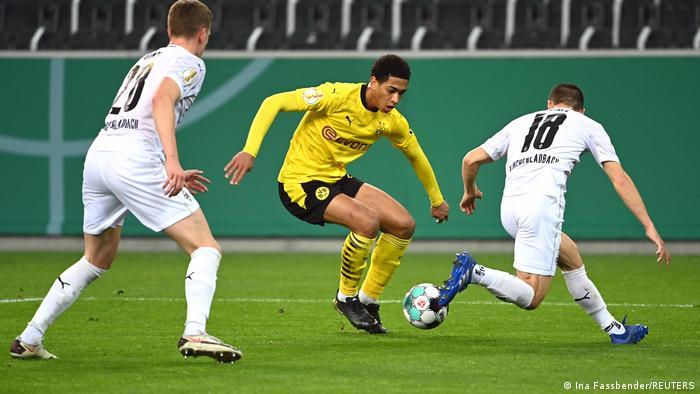 Dortmunds Jude Bellingham (M.) setzt sich gegen zwei Gladbacher Gegenspieler durch