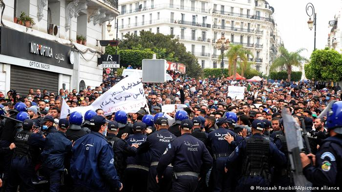 Police officers block the road as Algerian anti-government protesters take the streets of the capital Algiers within Hirak pro-democracy movement demonstrations in Algeria on March 1, 2021.