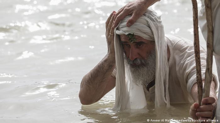 Un hombre lavándose la cara en el río Tigris