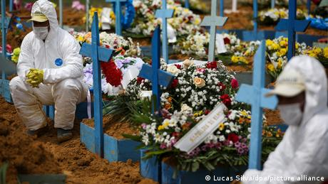 Cemetery workers are forced to don protective clothing during a funeral service in Manaus
