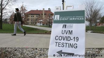 Студент проходит мимо таблички с указателем Центр тестирования на коронавирус