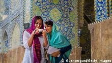 Young female western tourist is showing her images on the camera display to her female iranian tourguide . Both are wearing the typcial simple headscarf (hijab or rousari) while they are visiting a mosque in Isfahan, iran.