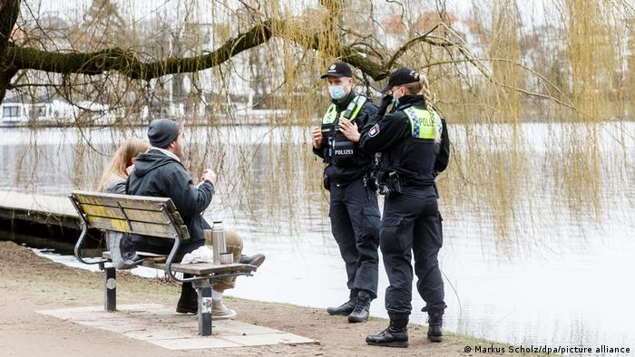 Two police officers talking to a couple on a bench because they are not wearing masks