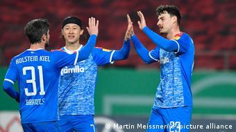 Drei Kieler Spieler klatschen sich ab.