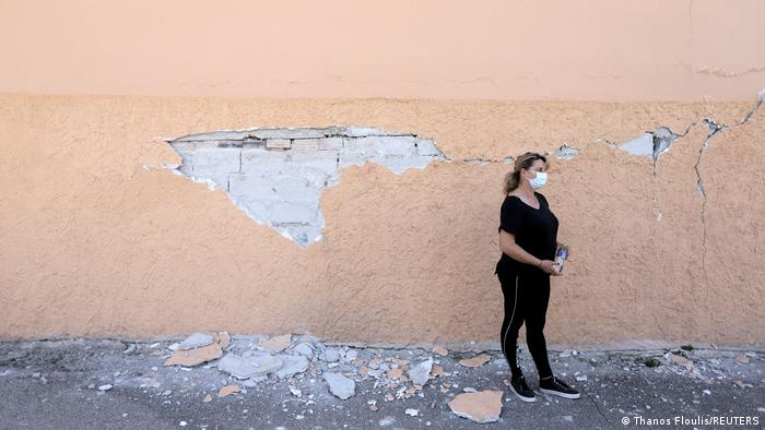 a local woman wears all black and a face mask while standing next to a cracked wall