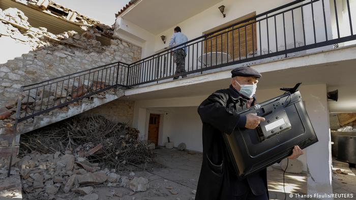 a man carries a TV from his damaged house following an earthquake in the village of Damasi, in central Greece