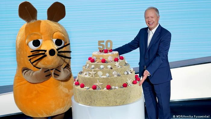 The Maus mascot receiving a birthday cake from ARD chief Tom Buhrow in January 2021