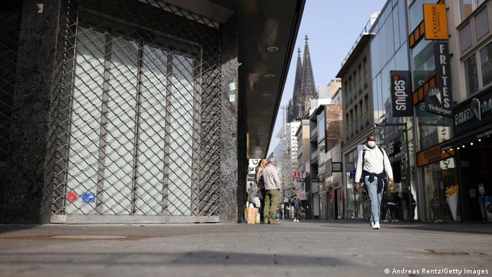 A pedestrian walks past a closed retail shop on the Cologne shopping mile