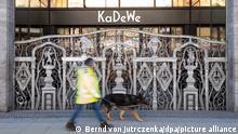 Ein Mann mit Hund geht am geschlossenen Gitter vor dem Haupteingang vom Kaufhaus des Westens (Kadewe) vorbei . Bund und Länder beraten in einer Videokonferenz darüber, unter welchen Umständen die aktuellen Corona-Beschränkungen in Deutschland gelockert werden können. +++ dpa-Bildfunk +++