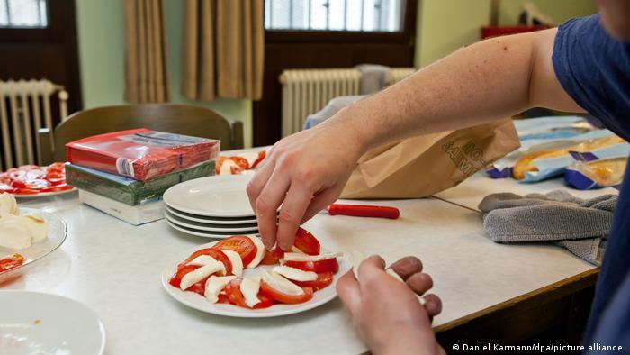 Заключенный тюрьмы в Нюрнберге раскладывает на тарелке сыр и помидоры