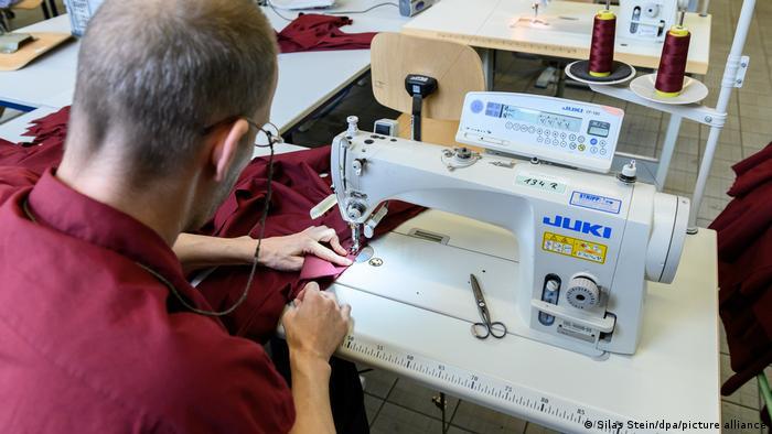 Заключенный сидит перед швейной машинкой