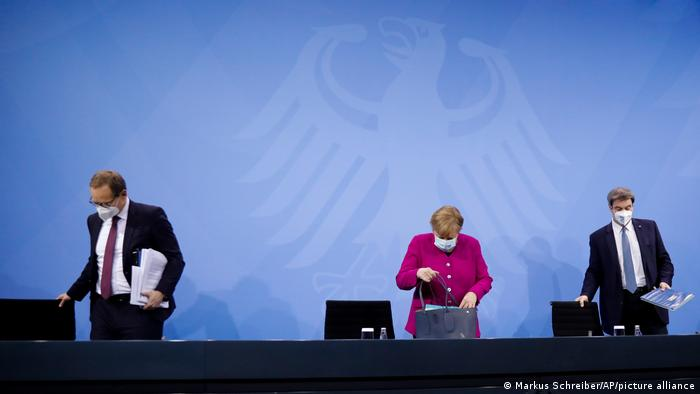 German Chancellor Angela Merkel, center, Bavarian state premier Markus Soeder, right, and the Mayor of Berlin Michael Mueller, left