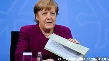 Angela Merkel bei einer Pressekonferenz. In ihrer linken Hand hält sie eine Mappe mit Unterlagen