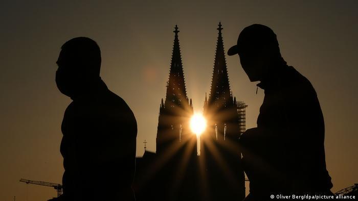 Foto mostra a silhueta de duas pessoas andando em frente à Catedral de Colônia, com o sol brilhando entre as duas torres da igreja