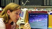 A stock trader at the stock exchange in Frankfurt, Germany, phones in front of a TV screen during the World Cup soccer game Turkey vs Brasil on Monday, June 3, 2002. (AP Photo/Bernd Kammerer)