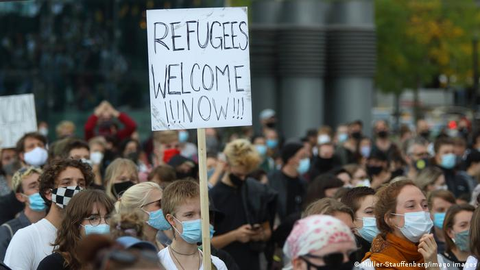 Demonstration by people in face masks demanding that Germany take in refugees