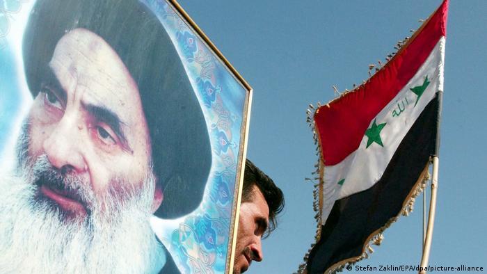 أحد المتظاهرين العراقيين يحمل صورة علي السيستاني (بغداد 8 يونيو 2004)