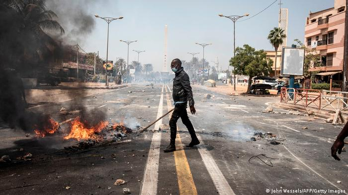 A Senegalese police officer carries a stick as he clears away a fire